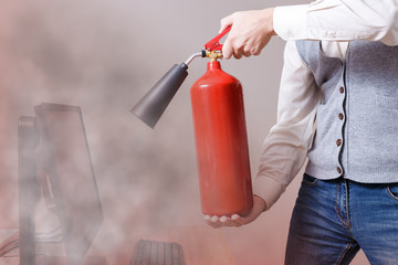 Man using fire extinguisher to stop fire in the apartment. Concept of protection and security