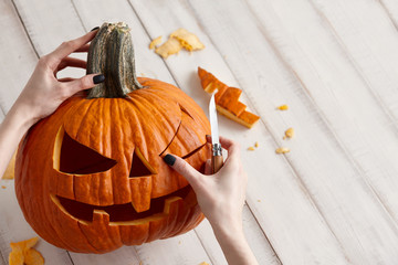 Woman carving big orange pumpkin into jack-o-lantern for Halloween holiday decoration on white wooden planks, close up view
