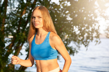 A girl with long red hair in a blue top runs in the morning along the waterfront along the sea.