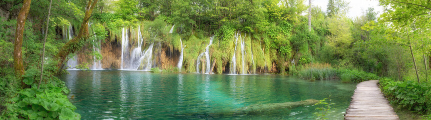 Last sunlight lights up the pure water waterfall on Plitvice National Park. Colorful spring panorama of green forest with blue lake. Great countryside view of Croatia, Europe.