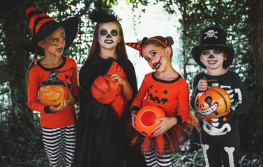 happy Halloween! a group of children in suits and with pumpkins in forest
