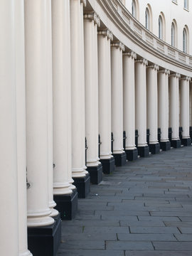 Perspective view of white columns of stuccoed terraced townhouses in London.