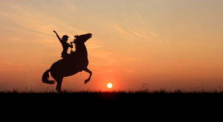 Cowgirl riding a horse, rearing up at sunset. Stallion standing on hind legs at horizon line with setting sun.