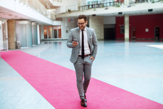 Handsome full of confidence young businessman walking through modern building and checking his phone.