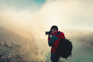 Photographer is shooting picture on top of mountain at sunrise scene, Kawah Ijen volcano