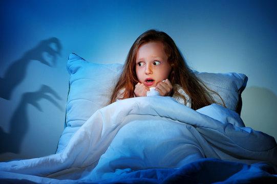 Sleepless girl in her bed having fears of night monsters
