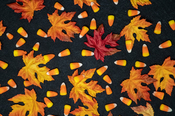 Candy corn and colorful maple leaves in an autumn scene over a black background