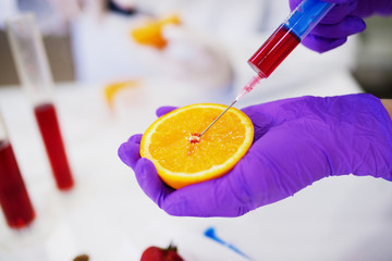 Close up of a hand in a protective glove holding orange and taking a sample from it with a syringe.