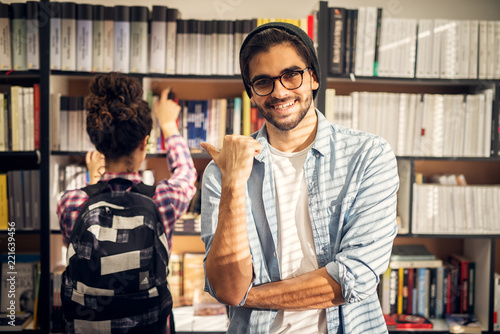 Portrait Of A Cute Hipster Boy Showing On His Partner In Studying Standing Front