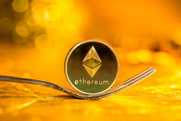 Ethereum cryptocurreny fork concept on a shining gold background