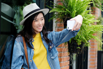 Young cute asian woman in casual style making selfie with her smartphone in the urban city outdoors background, woman selfie,  people outdoors with technology, travel and lifestyle concept