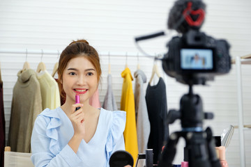 Young asian woman beauty blogger showing cosmetic while recording how to make up video tutorial by camera, vlog concept, beauty and fashion people and technology communication