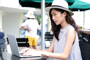 Young asian woman using laptop computer sitting at cafe city outdoors, working outdoors, people and technology, lifestyles, education, business concept