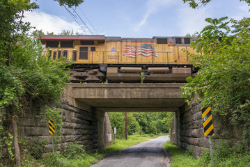 An orange train streaks across a concrete and stone bridge overpass and a lonely country gravel road.