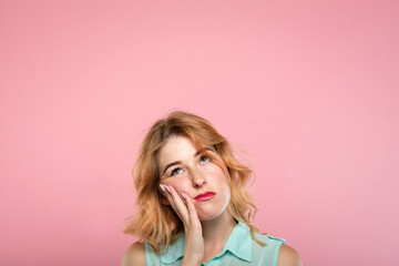 facial expression. low mood and emotion. bored unimpressed disinterested woman looking up. young beautiful blond girl portrait on pink background.