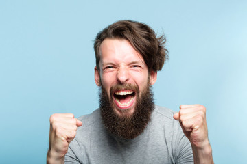 yes success and achievement. happy overexcited enthusiastic exhilarated guy making a win gesture and screaming. thrilled man portrait on blue background.