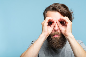 funny ludicrous joyful comic playful man pretending to look through binoculars made of hands. portrait of a young bearded guy on blue background. emotion facial expression concept Wall mural