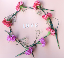 love wooden word  with fresh flowers geometric frame on  pale pink background