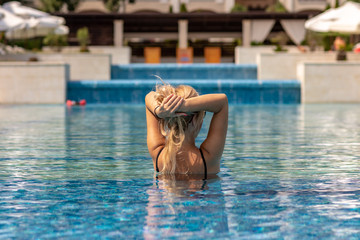 Blonde woman holding her hair in the swimming pool in luxury resort.