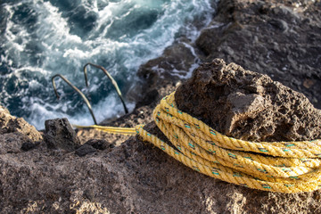 Aluminum ladder, tied with a yellow rope to the rock on the ocean