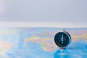 Compass on the background of the geographical map - the theme of travel