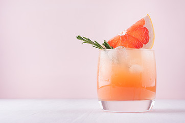 Foto op Canvas Cocktail Cold fresh homemade grapefruit cocktail with ice, rosemary and pieces citrus on pastel pink background.