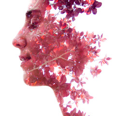 Double exposure profile portrait of a beautiful girl combined with natural elements creating an unusual effect where her face disappears behind red autumn leaves