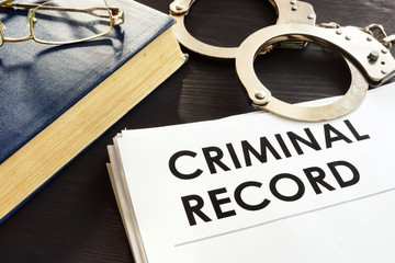 Criminal record and handcuffs on a desk. - fototapety na wymiar