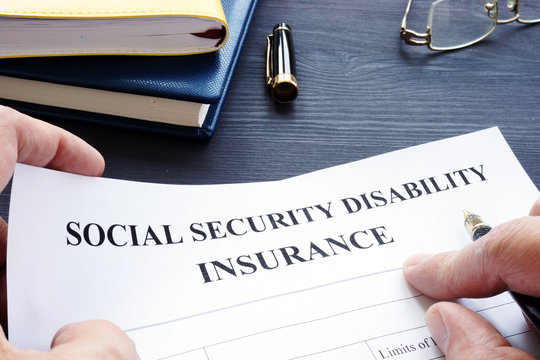 Man is holding Social Security Disability Insurance SSDI policy.