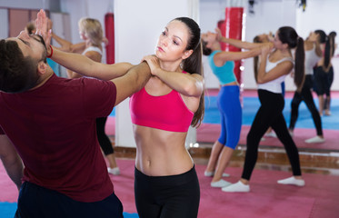 Young woman is practicing self-defence moves in pair