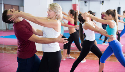 Female is training self-defence moves in pair with trainer
