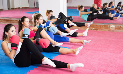 Group of women are doing exercise sitting