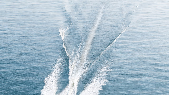 Beautiful waves of a trail on the water surface in the sea after a motorboat. Aerial flight bird view, background.