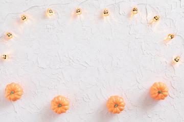Halloween frame with orange pumpkin, jack-o-lantern garlands on white background. Flat lay, top view