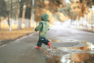 girl runs around the puddles in the autumn park, childhood game