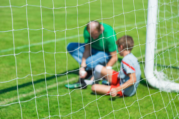 Blurred picture of a young injured male soccer or football player being treated by male team physician in front of the team goal