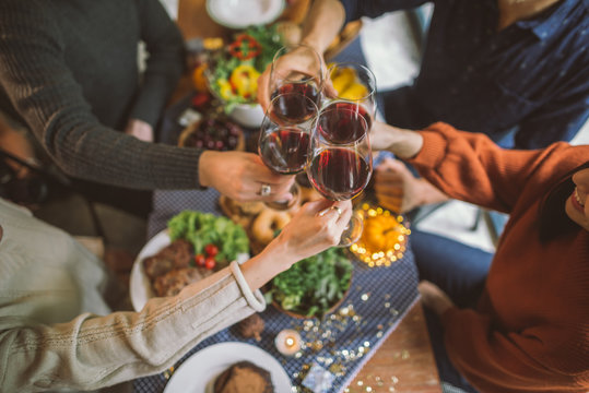 Friends clinking glasses above food on dinner table