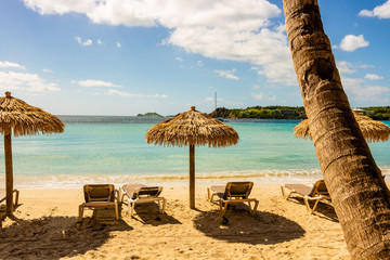 Emerald Beach in St. Thomas, USVI. Caribbean paradise with golden sands and turquoise water.  Empty beach resort with sunbeds and umbrellas.