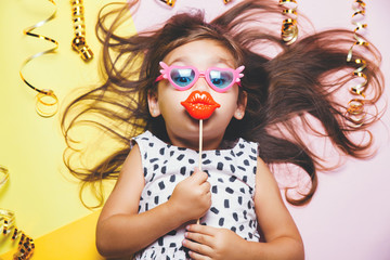 Cute little girl in funny glasses with plastic masquerade lips on stick.