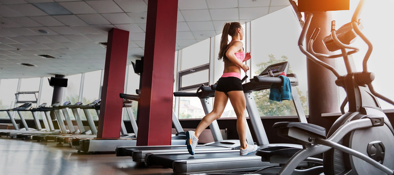 slim beautiful sporty woman running at the treadmill in the gym. Concept of cardio exercises and healthy way of life