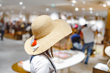 Asian Woman in a shopping Mall Trying hats and making fun.