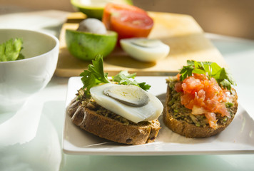 2, two sandwiches with avocado and tomato and boiled egg on a plate, chopped avocado and tomatoes on bread pieces, healthy Breakfast, food