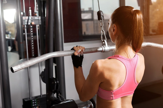 athletic woman wearing pink professional sportswear pumping an iron barbell at the sun lightened gym. healthy lifestyle concept