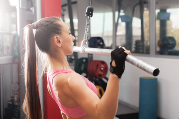 athletic girl with a ponytale wearing pink and black professional sportswear exercising with an iron barbell at the highly equipped gym. Strength and motivation concept