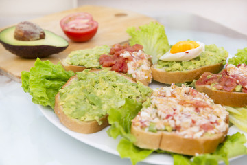 sandwiches with avocado, egg and tomato on lettuce leaves on a plate, breakfast,  a healthy snack