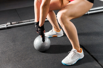 athletic woman wearing pink and black professional sportswear exercising with a kettlebell at the gym. Strength and motivation concept. close up photo of legs