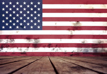 The flag of USA on a wall of plaster and the wooden floor.