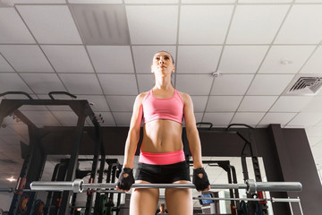 woman with a ponytale wearing pink and black professional sportswear squatting with an iron barbell at the highly equipped gym. fitness and workout concept