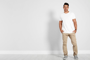 Full length portrait of handsome young man and space for text on white wall background Wall mural