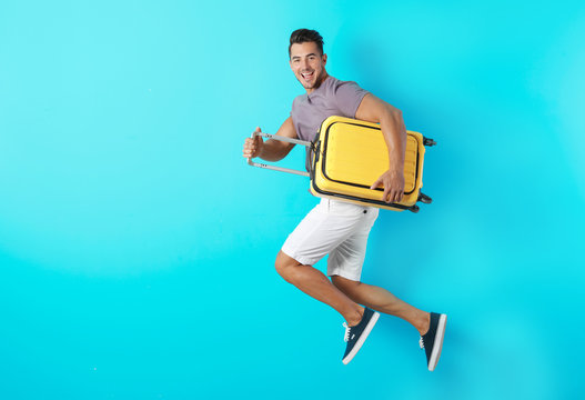 Young man jumping with suitcase on color background. Space for text